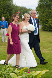 bride walking down the isle with parents and cream silk wedding bouquet with lace tulle pearls